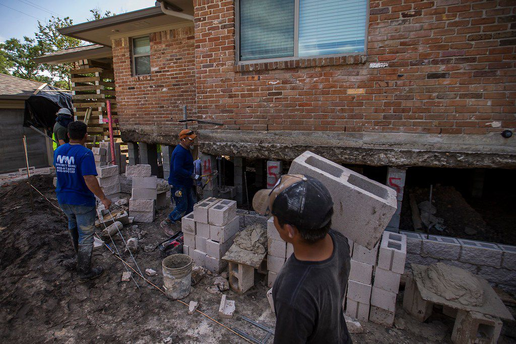 A house is raised as part of home elevation efforts in the Meyerland neighborhood, a few blocks from Brays Bayou, on Saturday, Aug. 11, 2018, in Houston. The area was flooded due to Hurricane Harvey.  (Smiley N. Pool/The Dallas Morning News)