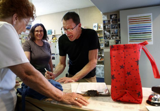 Brian Riggs, a longtime employee of Lucky Dog Books, chats with his customer Louise Kirby, far left, at the store in Lochwood neighborhood in Dallas, TX on August 23, 2013. Far background is another employee Elizabeth Dockendorf.