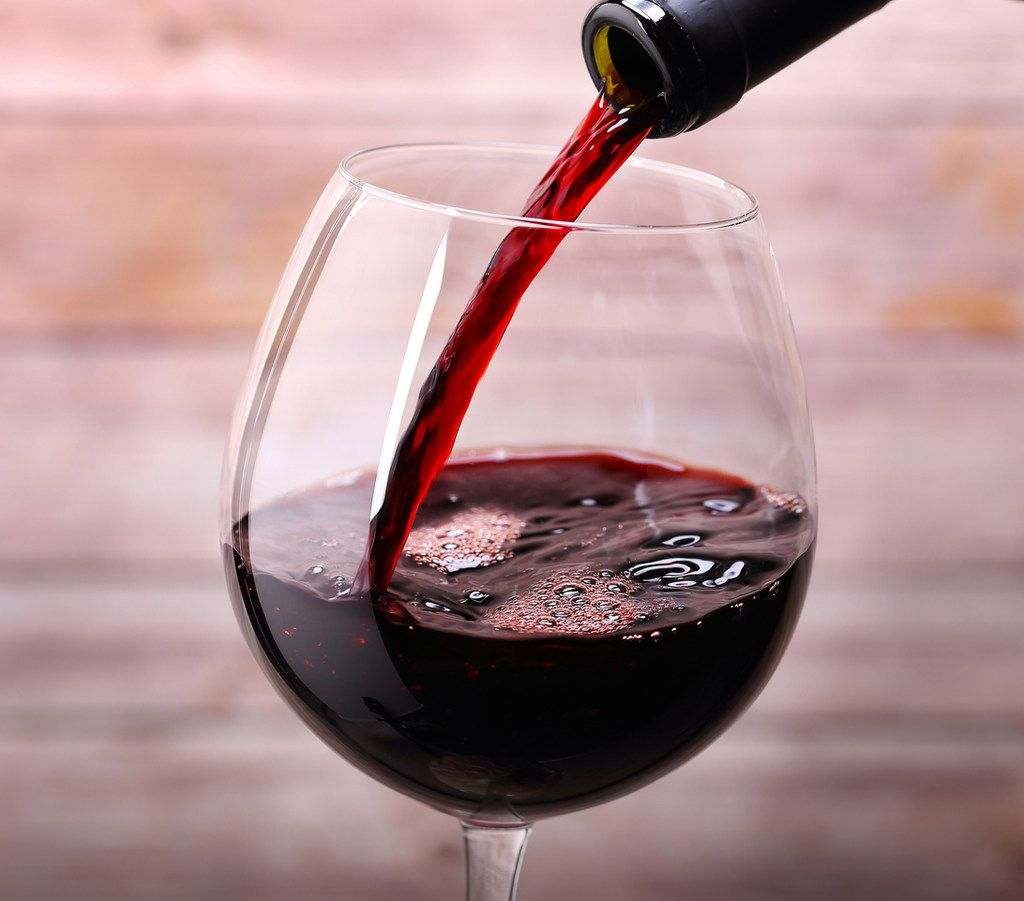 Pouring red luxury wine into glass and wooden background