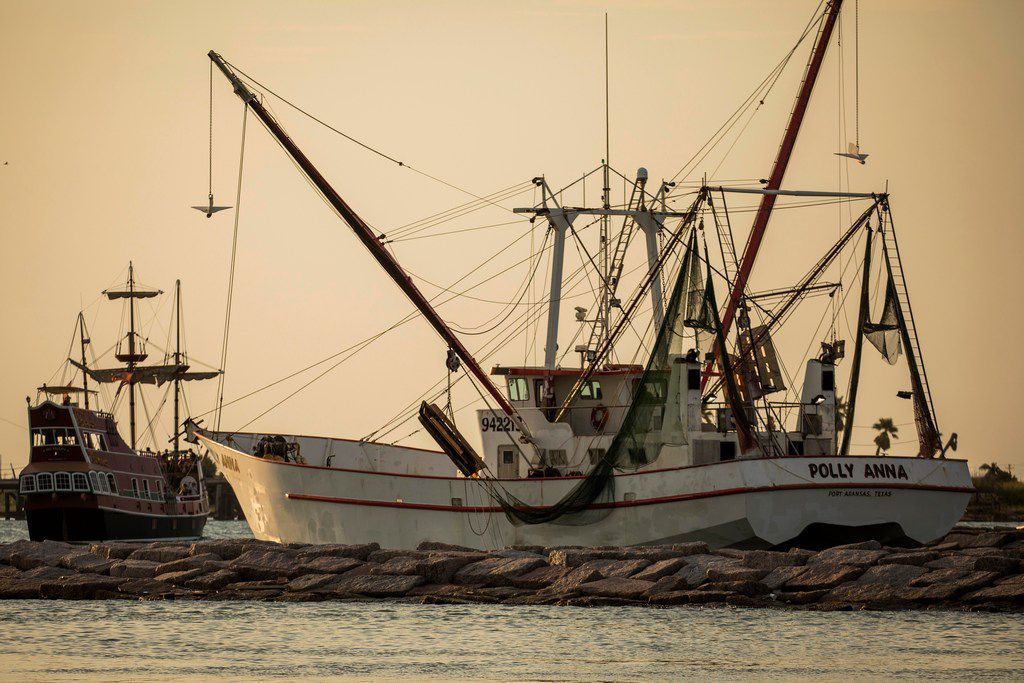 The Polly Anna shrimp boat follows the Red Dragon Pirate Cruise as both head out in late July from the Dennis Dryer Municipal Harbor in Port Aransas, Texas.