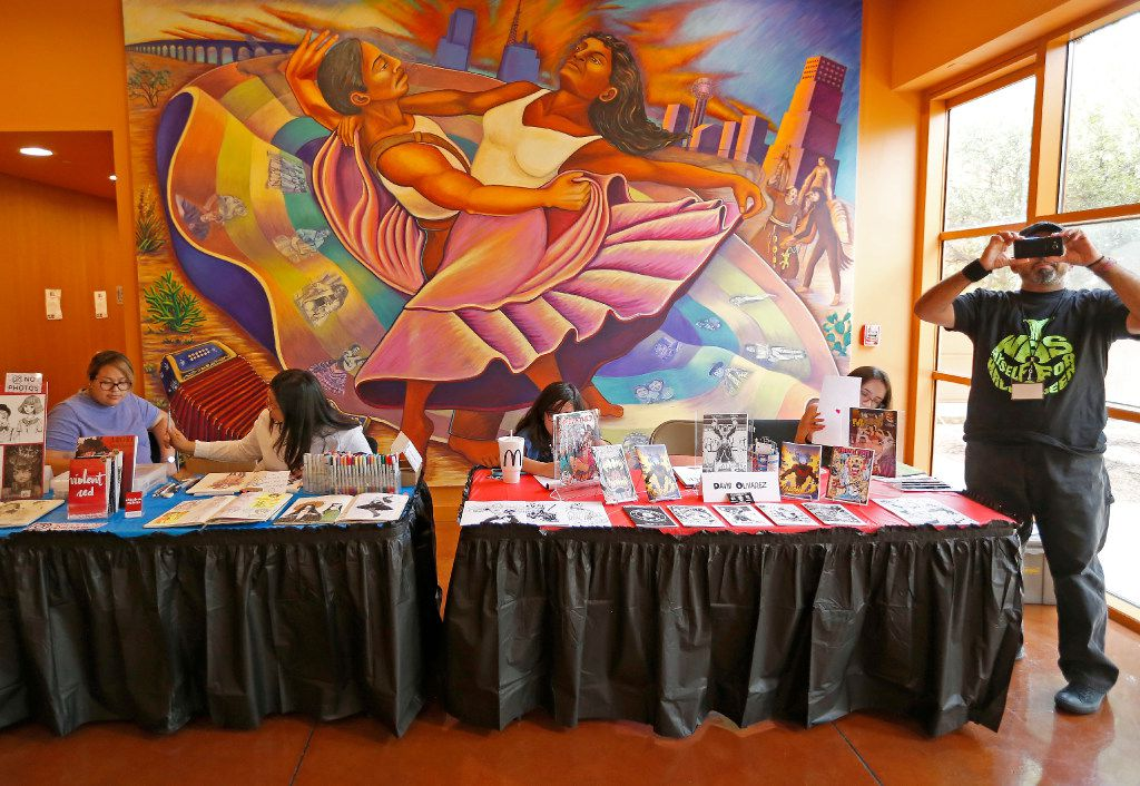 Comic book artist David Olivarez (right) uses his cell phone to record video next to his table during Texas Latino Comic Con at Latino Cultural Center in Dallas, Saturday, July 29, 2017. (Jae S. Lee/The Dallas Morning News)
