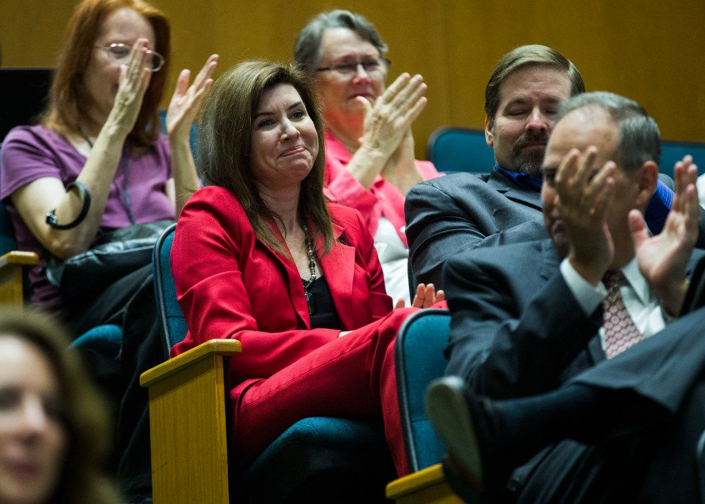 Former City Council member Angela Hunt (second from left), the leading voice against the Trinity River toll road, applauds after the Dallas City Council voted to kill the toll road on Wednesday.