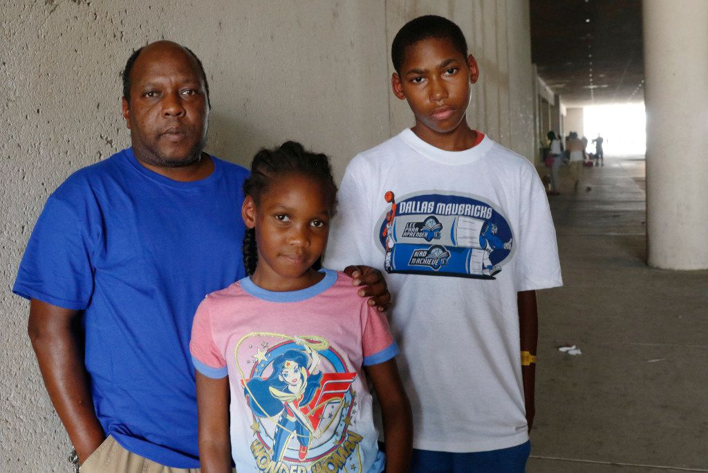 Stacey Stewart poses with his children, Destiny, 10,  center, and Ja'Cobie, 14, by the KBH Convention Center Mega Shelter in downtown Dallas on Monday, September 4, 2017. They evacuated from Port Arthur, Texas after Hurricane Harvey flooded their apartment last week.
