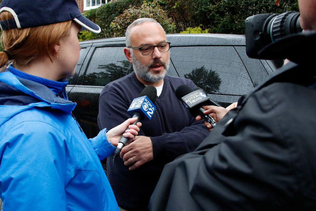 """Jeff Finkelstein, center, president and CEO of the Jewish Federation of Greater Pittsburgh, is interviewed several blocks from the Tree of Life Synagogue where a shooter opened fire Saturday, Oct. 27, 2018, wounding multiple police officers and causing """"multiple casualties"""" according to police. (AP Photo/Gene J. Puskar)"""