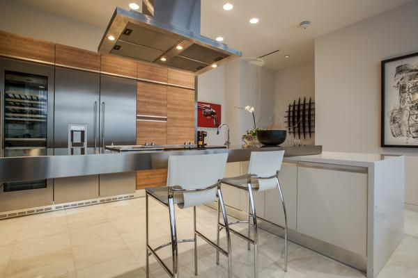 Purchased as unit from Cantoni, the contemporary kitchen has custom cabinetry, a stainless-steel island and sleek Gaggenau appliances.