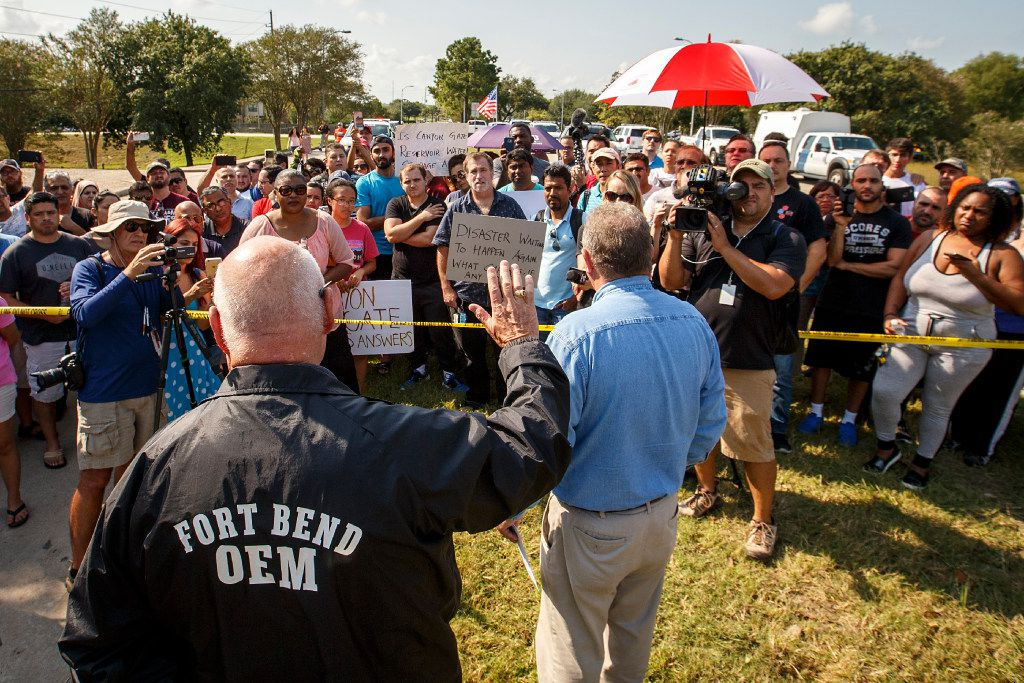 Fort Bend County Judge Robert Hebert raises his hand as he takes questions from Cinco Ranch Canyon Gate subdivision residents who gathered to demonstrate at a police road clock outside their neighborhood on Saturday, Sept. 2, 2017, in Katy, Texas. The area remains cordoned off due to flood waters left by Hurricane Harvey.