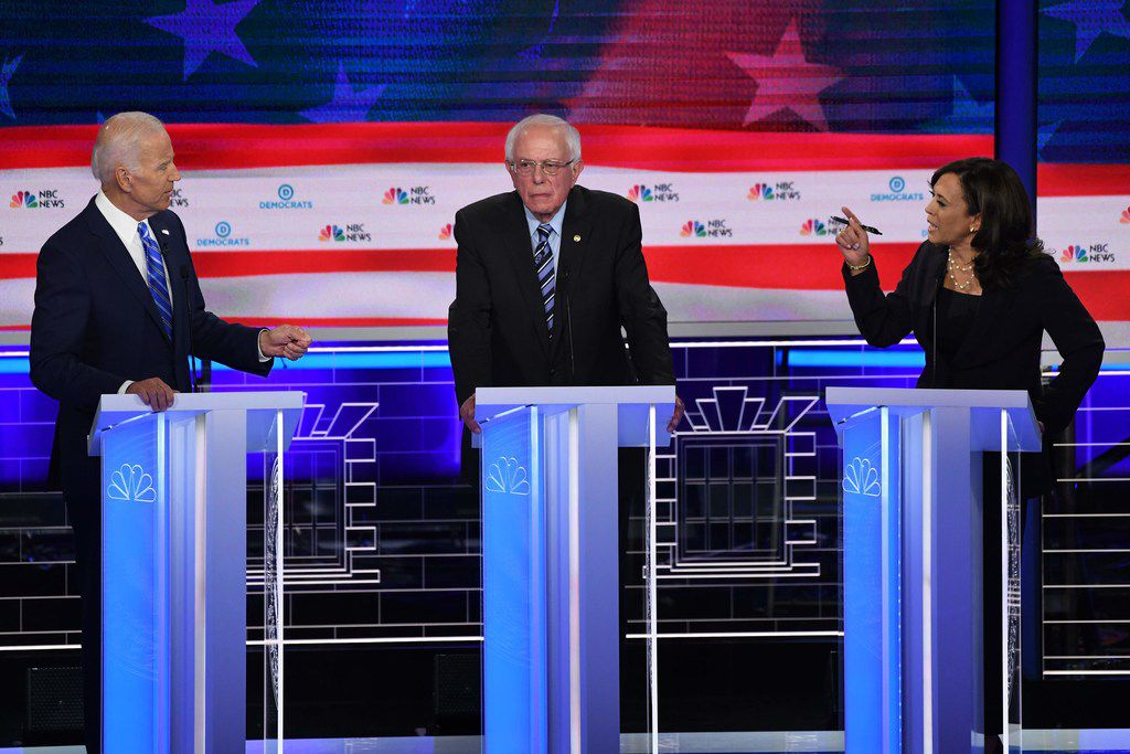 Democratic presidential hopefuls Joe Biden and Kamala Harris speak across candidate Bernie Sanders during the first round of debates in June.