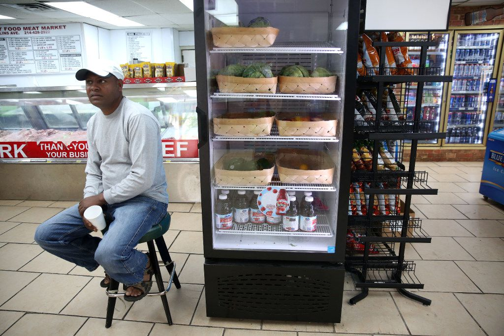 Owner Asnake Tarekegn talks to a customer next to the refrigerator at Hackney Food in the Mill City neighborhood in South Dallas. (Rose Baca/The Dallas Morning News)