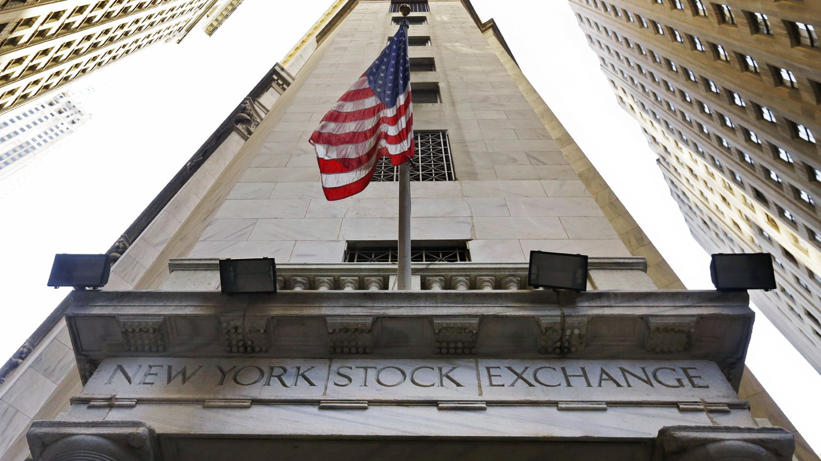 The American flag flies above the Wall Street entrance to the New York Stock Exchange. Probably not moving to Dallas any time soon. (File Photo/The Associated Press)