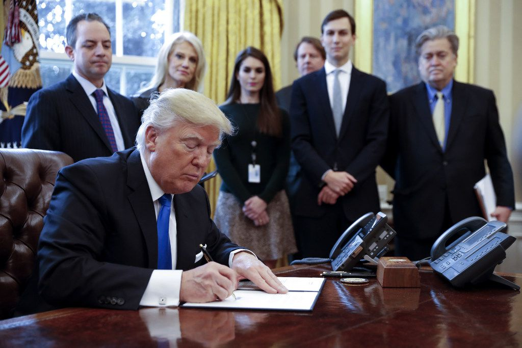 President Donald Trump signs one of five executive orders related to the oil pipeline industry in the Oval Office of the White House in Washington, D.C. on Tuesday. Trump took steps to advance construction of the Keystone XL and Dakota Access oil pipelines. (Shawn Thew/Pool photo via Bloomberg