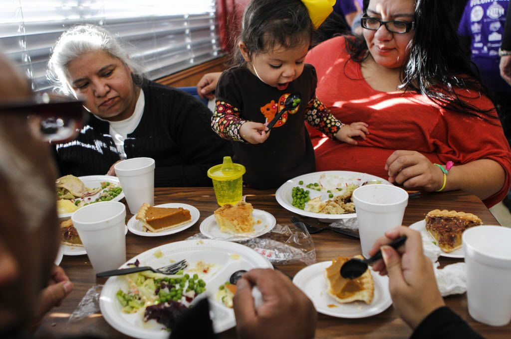 Eighteen-month old Bethany Martinez, center, eats some peas while enjoying a free Thanksgiving Day meal at Norma's Cafe in Oak Cliff.