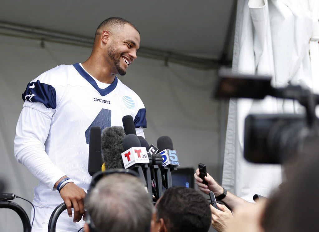 Dallas Cowboys quarterback Dak Prescott (4) laughs after a question as he answers questions from the media after the morning walk through during training camp in Oxnard, California on Monday, July 24, 2017. (Vernon Bryant/The Dallas Morning News)