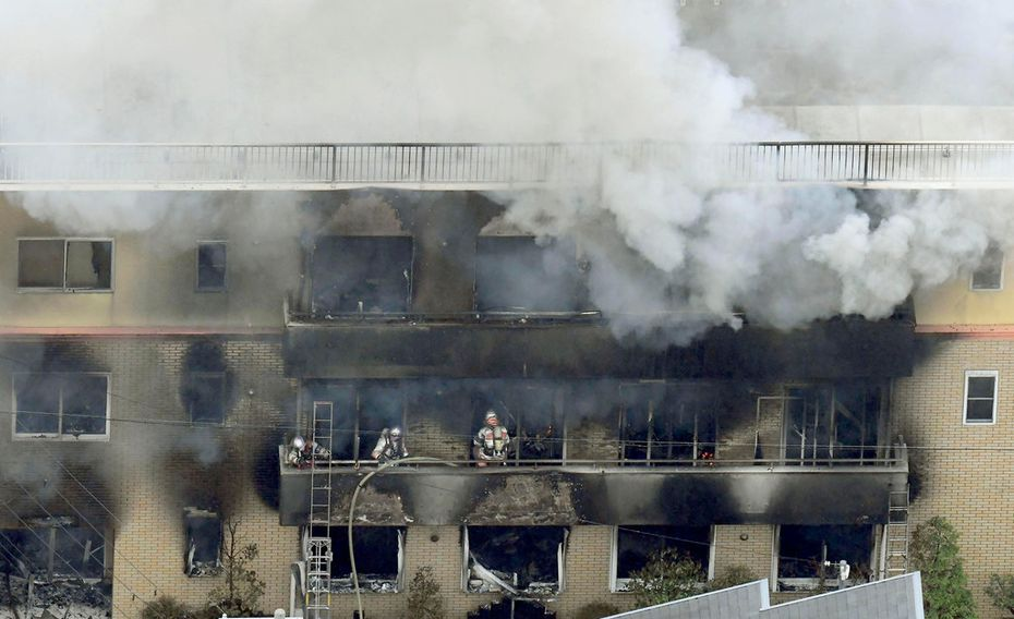 Firefighters work as smoke billows from a three-story building of Kyoto Animation in a fire in Kyoto, western Japan, Thursday, July 18, 2019.