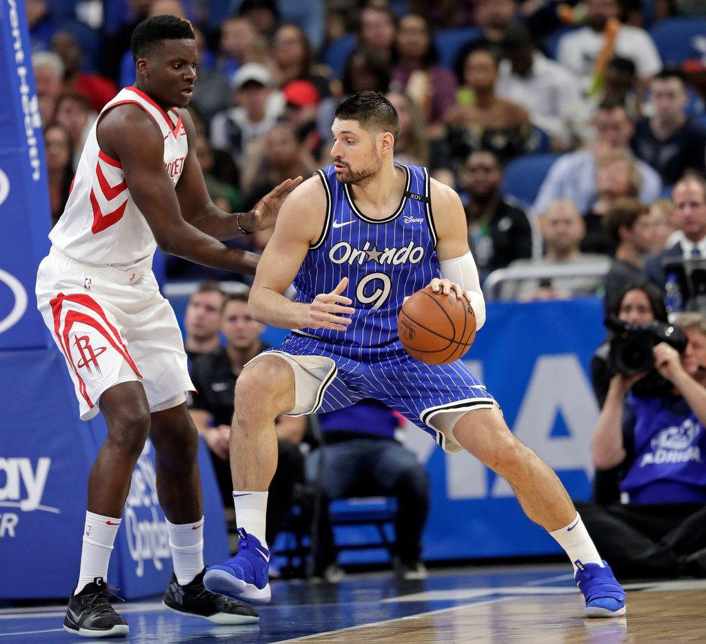 Orlando Magic's Nikola Vucevic (9) makes a move to get past Houston Rockets' Clint Capela, left, during the first half of an NBA basketball game, Sunday, Jan. 13, 2019, in Orlando, Fla. (AP Photo/John Raoux)