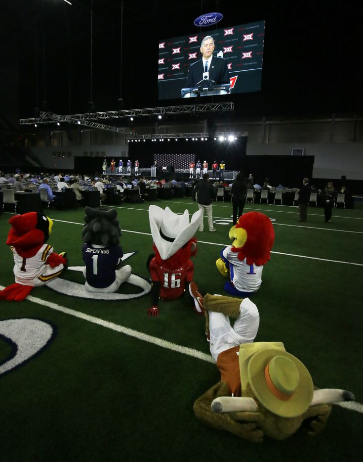 Mascots sit on the field while watching Big 12 commissioner Bob Bowlsby speak to reporters during the Big 12 NCAA college football media day at the Dallas Cowboys practice facilities in Frisco on July 17, 2017.