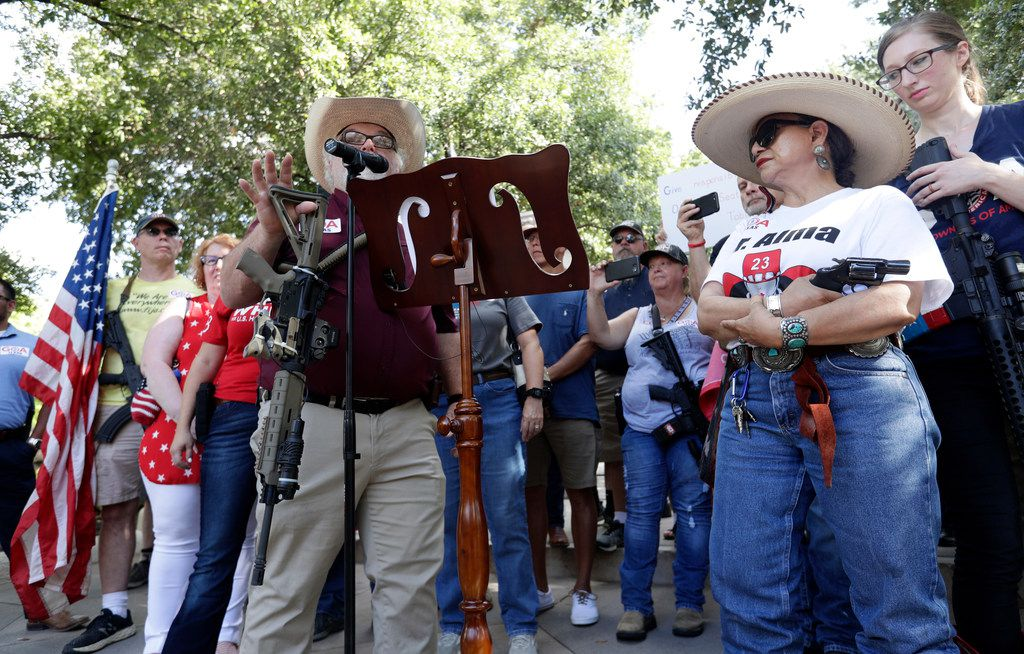 Steven Willeford holds up a rifle and Dr. Alma Arredondo-Lynch (right) holds a pistol as gun rights advocates gather outside the Texas Capitol where Gov. Greg Abbott held a round-table discussion about ways to combat extremism and keep Texans safe after a mass shooting in El Paso.