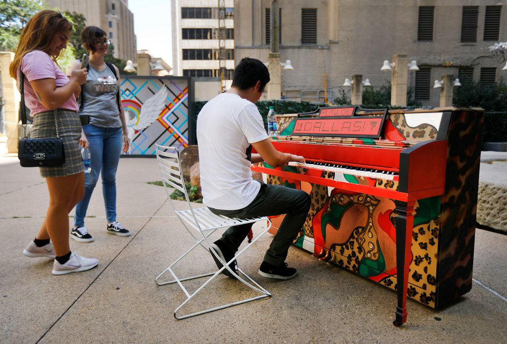 """Miguel Mendez of Dallas plays on artist Leigha Lugo's painted piano in Pegasus Plaza in downtown Dallas on July 14, 2018. Marina Buzin (left) and Livia Ferrari of Brazil watch their friend play. Lugo has been commissioned to paint each of these pianos in a fashion that captures the spirit of Dallas art and music. """"Play On, Dallas!"""" is a project by the Dallas Office of Cultural Affairs that placed painted pianos in the Dallas Farmers Market and Pegasus Plaza."""