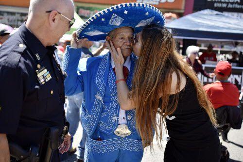 Deborah Luna le da un beso a Juan Palacio, de 86 años, luego de tomarse una foto con él durante el festejo del Cinco de Mayo en Oak Cliff.