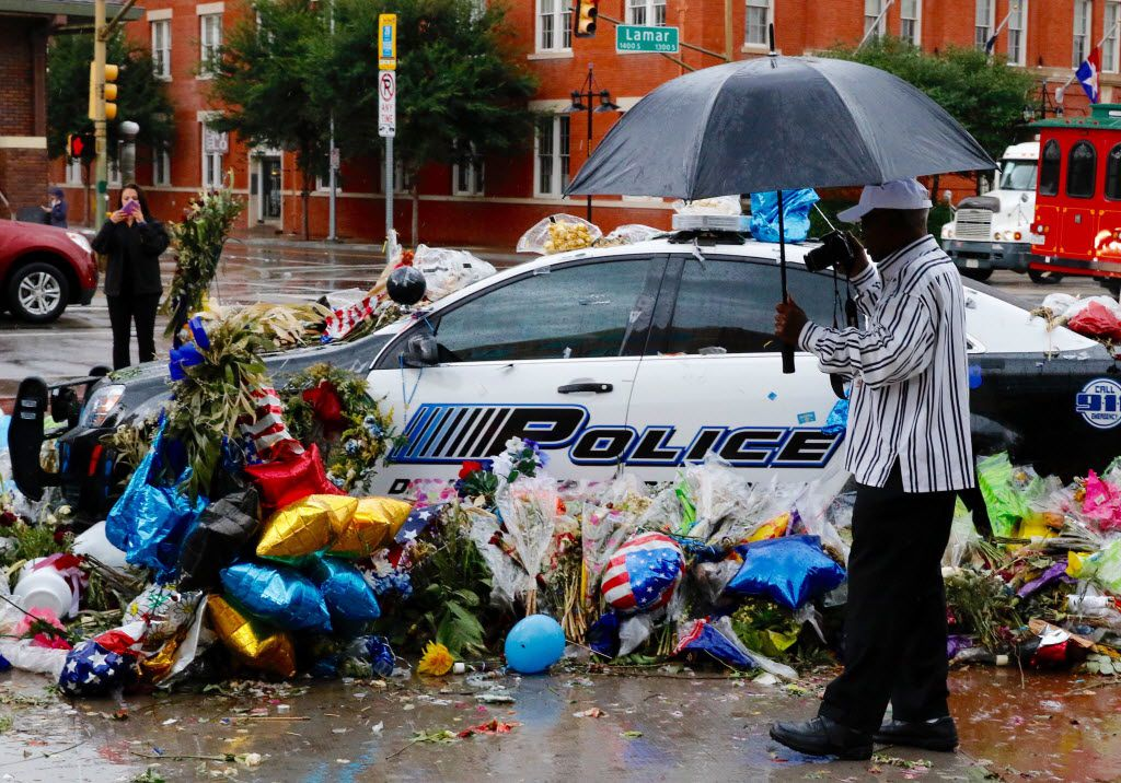 Thomas Freeney of Dallas takes photos of the memorial at the Dallas police headquarters in the rain on Friday, July 15, 2016. Five police officers were killed and seven others were injured in an ambush on July 7, 2016 during a march against recent police involved shootings. Investigators are saying the suspect is 25-year-old Micah Xavier Johnson of Mesquite, Texas. (David Woo/The Dallas Morning News)