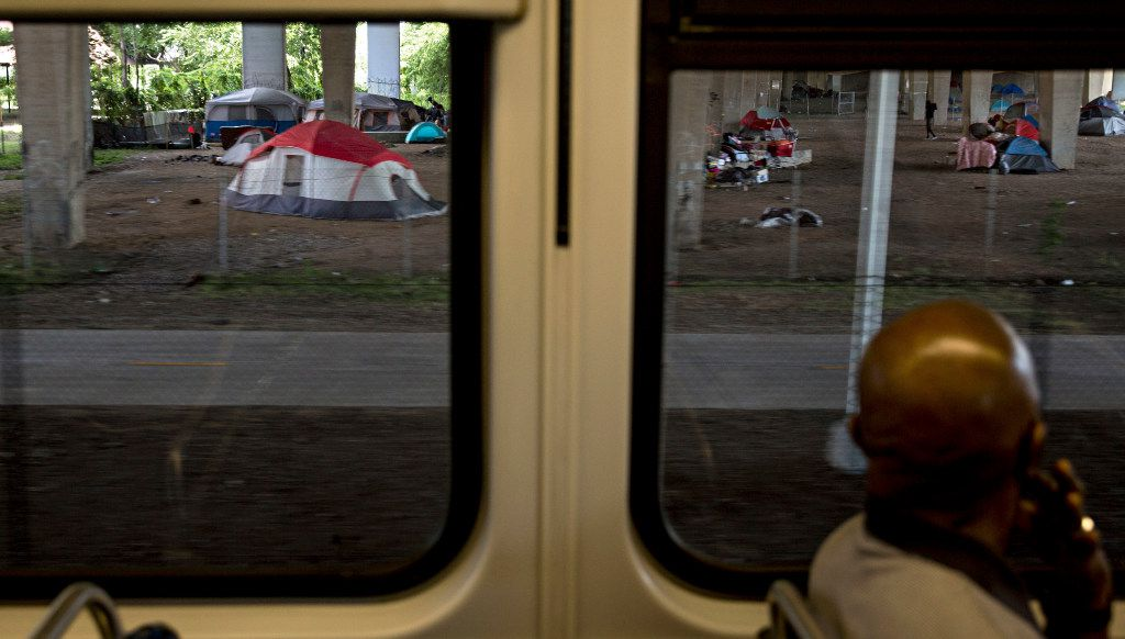 Tents and people in a homeless encampment under I-30 at Haskell Avenue can be seen from the westbound DART Green Line Tuesday, March 17, 2016 in Dallas. (G.J. McCarthy/The Dallas Morning News) ORG XMIT: DMN1605171253104282