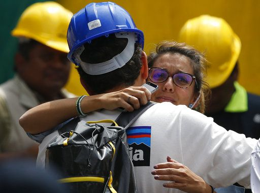 Un rescatista abraza a la novia de Jorge Gómez, de España, quien espera en un lugar de búsquedas por gente que se cree se encuentra atrapada debajo de los escomros de una edificio de oficinas, incluyendo su novio, en la esquina de Álvaro Obregón y Yucatán, en la Ciudad de México.