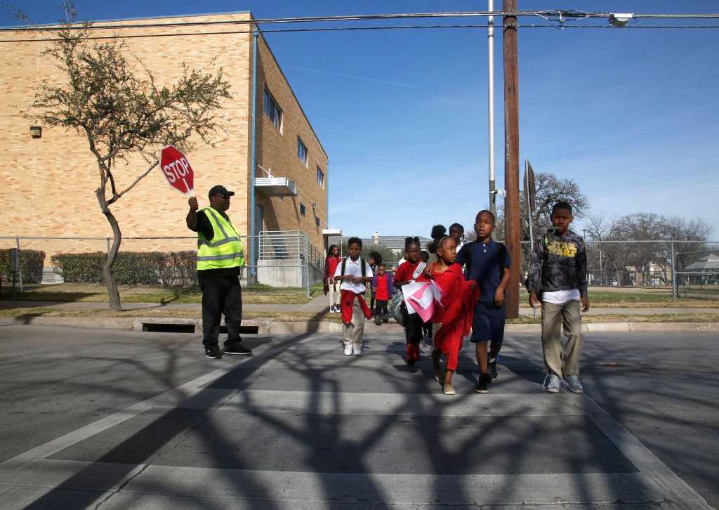 School crossing guard Derrick McMillon stopped traffic on North Washington Street in Dallas  as students left J. W. Ray Learning Center last February.