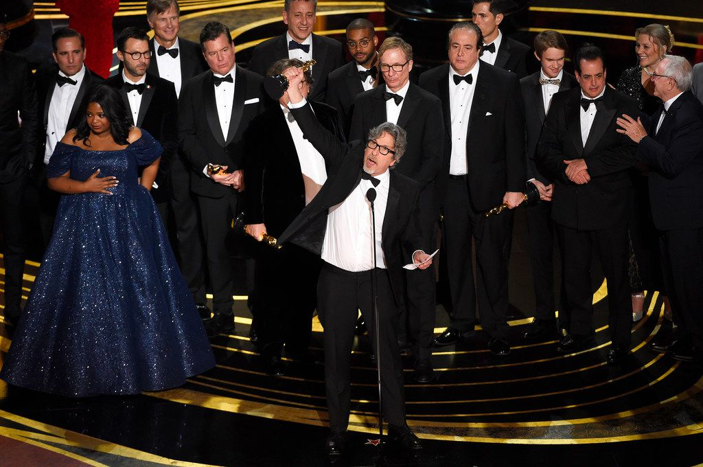 Peter Farrelly (center) and the cast and crew of Green Book accept the award for best picture at the Oscars.