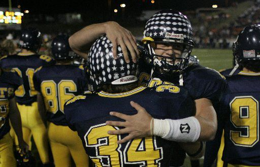 Highland Park QB Matthew Stafford celebrates with RB Alex Carroll (34) after Stafford's touchdown pass less a minute before halftime made the score 17-14 with the Scots trailing at the half against Texarkana Texas High in high school football playoff action at Rose Stadium in Tyler, Friday night, November 11, 2005.