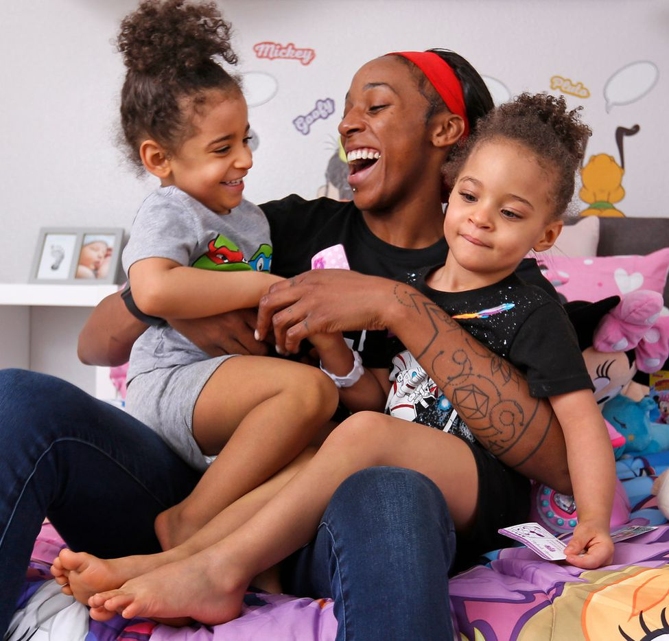 Dallas Wings' player Glory Johnson plays with her twin daughters Solei, left, and Ava in their bedroom at their home in Arlington, Texas, on Saturday, June 30, 2018. (Louis DeLuca/The Dallas Morning News)