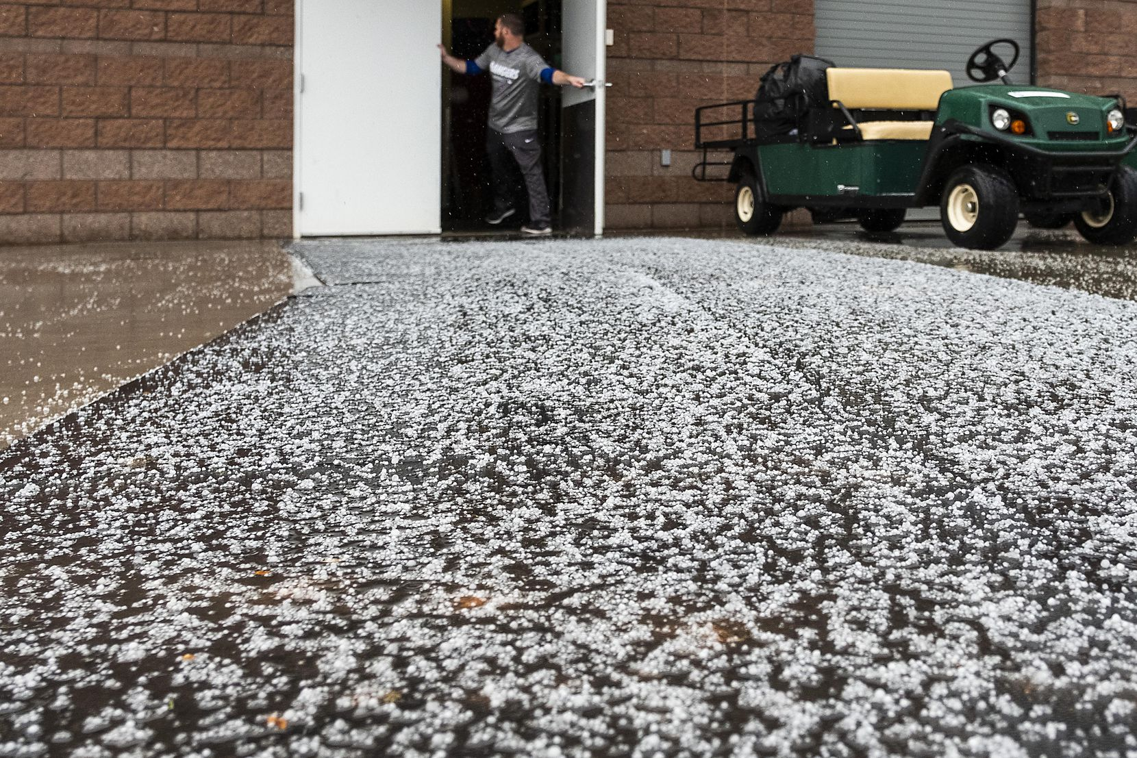 Snow pellets collect outside the Texas Rangers clubhouse door during a winter storm that hit following a spring training workout on Feb. 21 at the team's training facility in Surprise, Ariz.