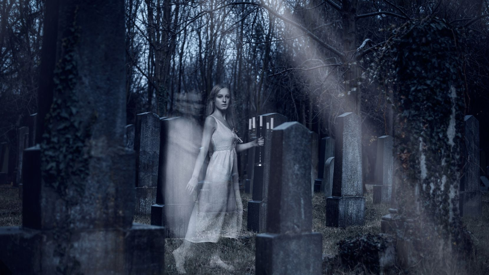 Ghost girl walking on cemetery. Halloween theme.