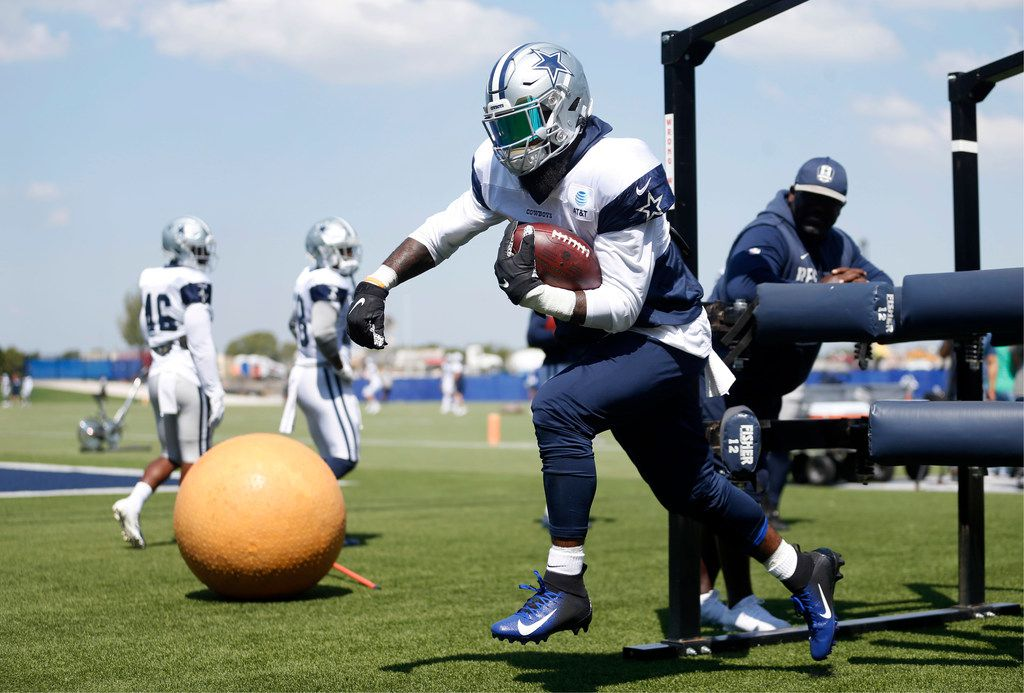 Dallas Cowboys running back Ezekiel Elliott (21) runs through drills with Dallas Cowboys running backs coach Gary Brown watching during practice at The Star in Frisco, Texas on Wednesday, September 4, 2019.