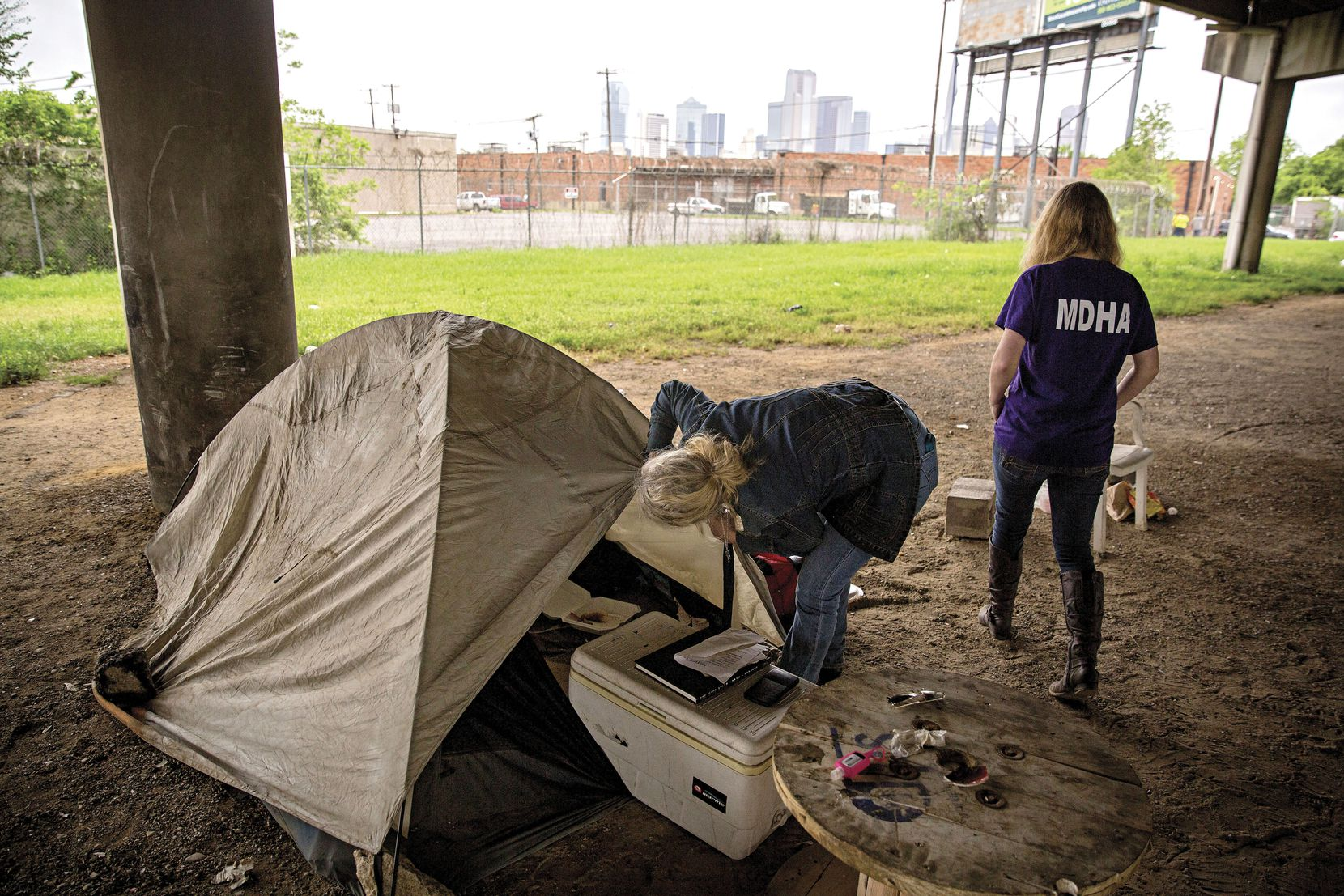 On April 19, Cindy Crain (left) and Rebecca Cox of the Metro Dallas Homeless Alliance sifted through belongings left in an abandoned section of the Tent City homeless camp in Dallas.