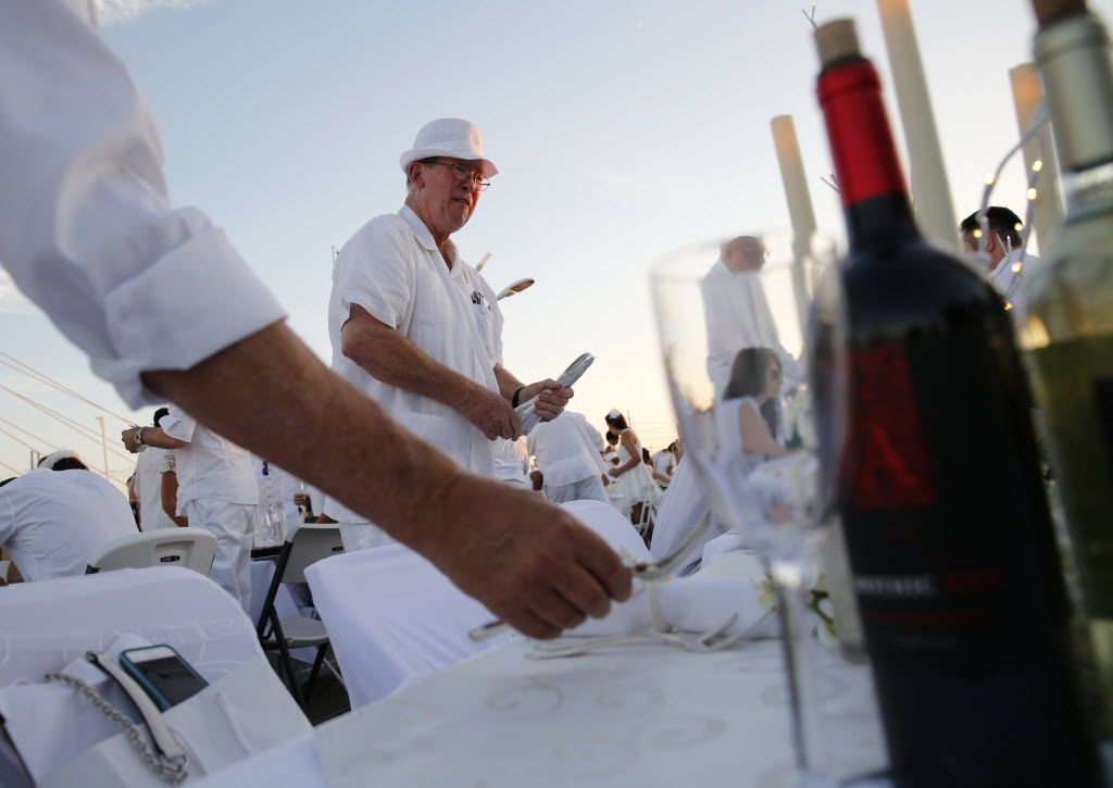 Lewis McMahan sets down silverware on the table during the inaugural Diner en Blanc Dallas on the Continental Avenue Bridge in Dallas on Sept. 17, 2015. Exactly 1,678 people attended the event, which requires dinner guests to dress all in white and bring their own tables, chairs and centerpieces. As per tradition, the location was kept private leading up to the event.