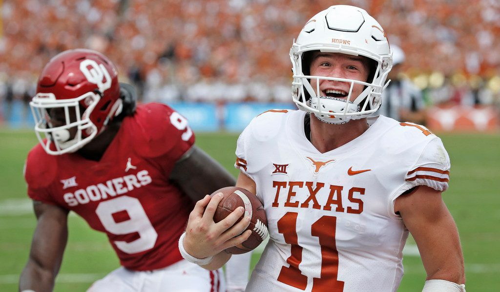 Texas Longhorns quarterback Sam Ehlinger (11) is all smiles as he scores a second-quarter touchdown, getting past Oklahoma Sooners linebacker Kenneth Murray (9) during the University of Texas Longhorns vs. the Oklahoma Sooners NCAA football game at the Cotton Bowl in Dallas on Saturday, October 6, 2018. (Louis DeLuca/The Dallas Morning News)