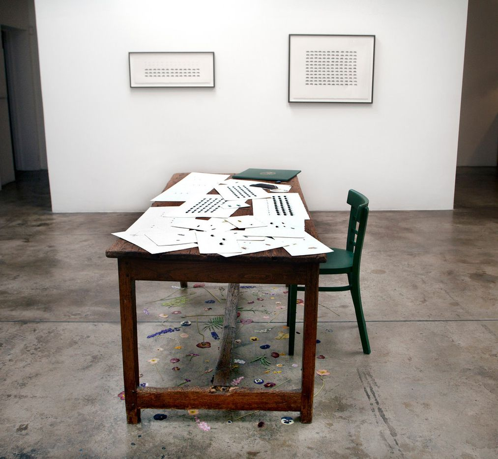 """Installation view of Battle Studies from the """"War Garden: series, 2018, watercolor and pencil on paper, military tacks, United States War Office document folder and painted metal, chair.  Photographed at the exhibition """"Cynthia Mulcahy: War Garden"""" at Talley Dunn Gallery in Dallas."""