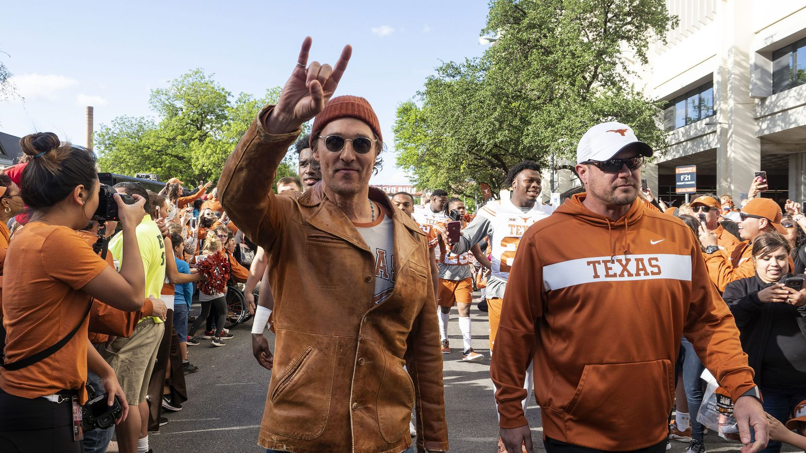 Actor Matthew McConaughey (left) and University of Texas football coach Tom Herman marched with players before the start of the Orange and White spring game in April.
