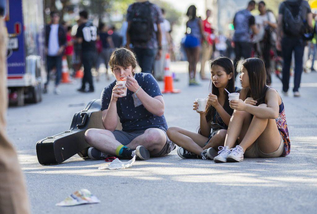 """Clark Gilchrist, 18, Laura Coon, 14, and Anna Gilchrist, 14, all of Austin, eat snow cones while sitting on Sixth Street after Clark played a street corner show during the SXSW music festival on Wednesday.  Gilchrist said, """"I made like five dollars."""""""
