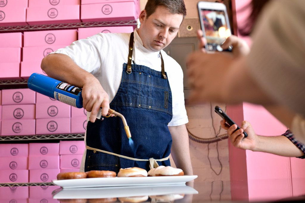 Executive chef Joe Baker uses a kitchen blowtorch to heat a sweet potato with maple marshmallow fluff during a revealing of the new donuts by Glazed Donut Works in Deep Ellum, on Wednesday, Nov. 16, 2016 in Dallas.