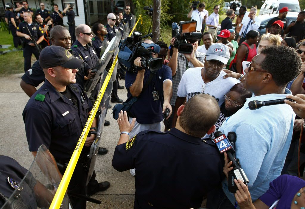 Dallas City Councilman Dwaine Caraway (right) tries to calm the emotions of family members including James White (wearing cap), the father of shooting victim James Harper.