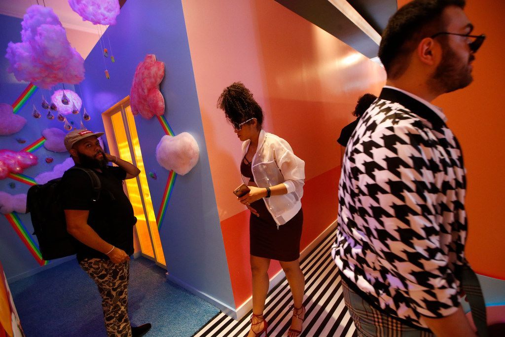 Artist Jeremy Biggers, (from left) Sam Lao and Christian Craven look around at Sweet Tooth Hotel in Dallas' Victory Park.