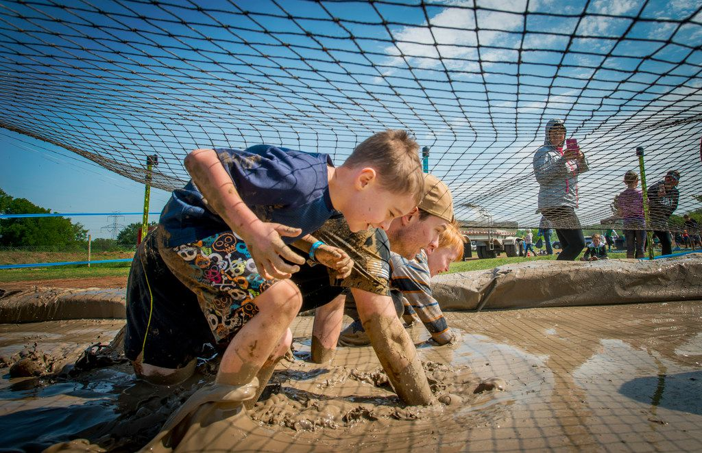 Competitors crawl through the mud pit during the Kids Obstacle Challenge.