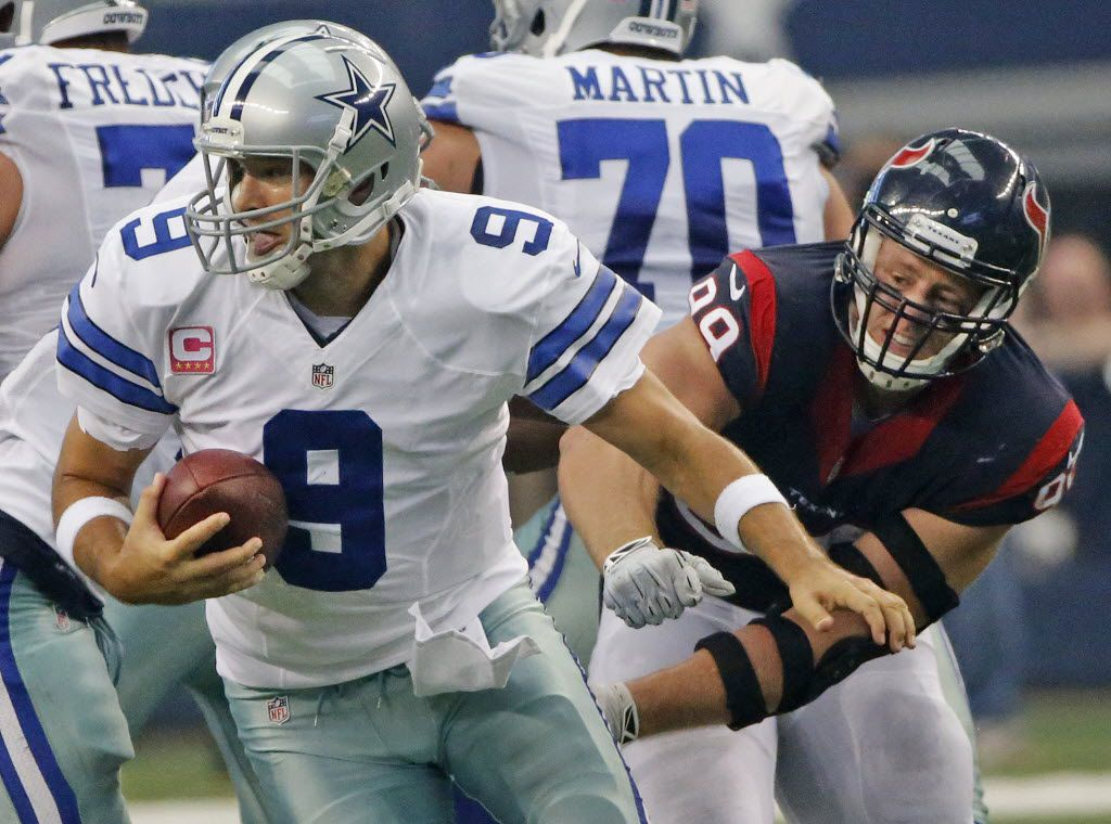 Dallas Cowboys quarterback Tony Romo (9) scrambles away from the pressure from Houston Texans defensive end J.J. Watt (99) in the second quarter during the Houston Texans vs. the Dallas Cowboys NFL football game at AT&T Stadium in Arlington on Sunday, October 5, 2014.  (Louis DeLuca/The Dallas Morning News)
