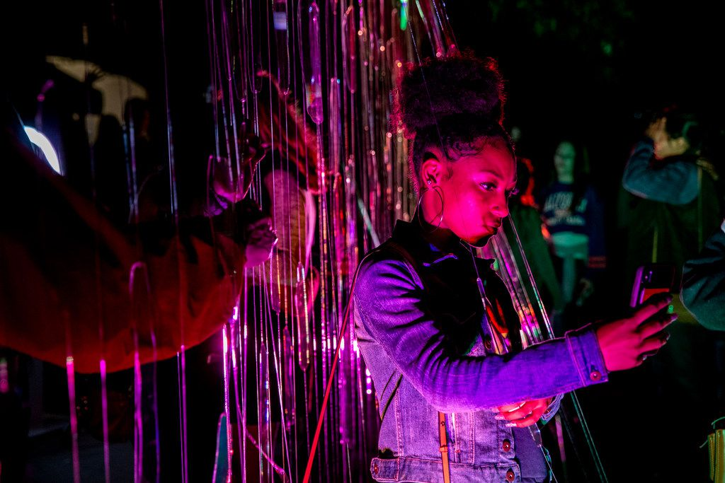 Chandler Garrison, 18, of Atlanta, takes a picture at an exhibit during AURORA in Downtown Dallas on Saturday, November 3, 2018