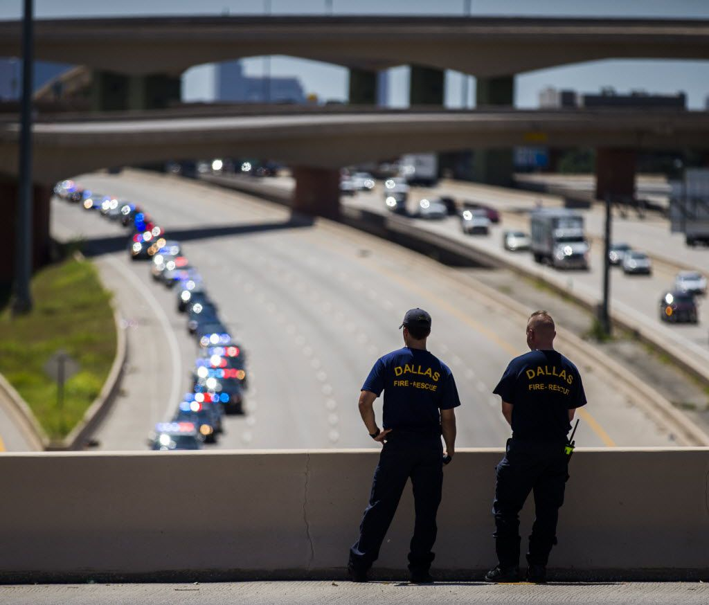 Dallas fire fighters Tyler McGuire (left) and Ken Burke (right) watch from an overpass as police vehicles proceed east on Interstate 635 to Restland Funeral Home, where Dallas police sergeant Michael Smith will be buried, on Thursday, July 14, 2016 close to TI Blvd in Dallas, Texas. Smith was one of five officers who were killed on Thursday, July 7, 2016, when a gunman targeted police during a Black Lives Matter rally in downtown Dallas. (Ashley Landis/The Dallas Morning News)