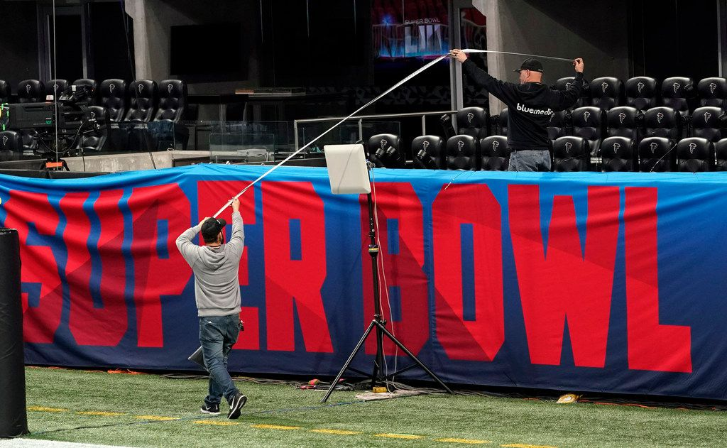 Workers use a tape measure as they hang a sign Jan. 29 inside Mercedes-Benz Stadium for Super Bowl 53 in Atlanta.