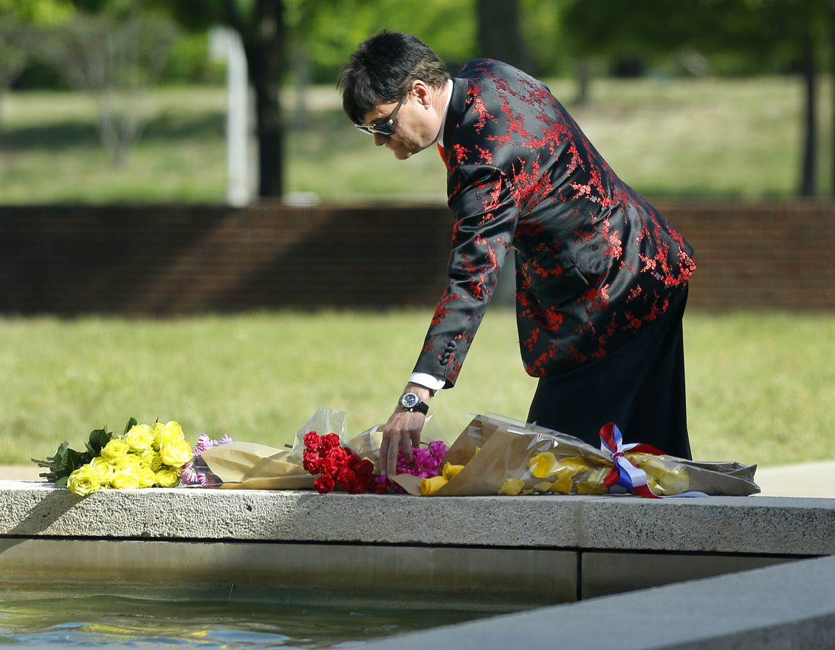 Steve Kemble leaves flowers in memory of former First Lady Barbara Bush at the fountain outside the George W. Bush Presidential Center in University Park, Texas, Wednesday, April 18, 2018. Kemble remembered using yellow roses, at the request of Mrs. Barbara Bush, to an event he was planning for the Bush family in 1997.