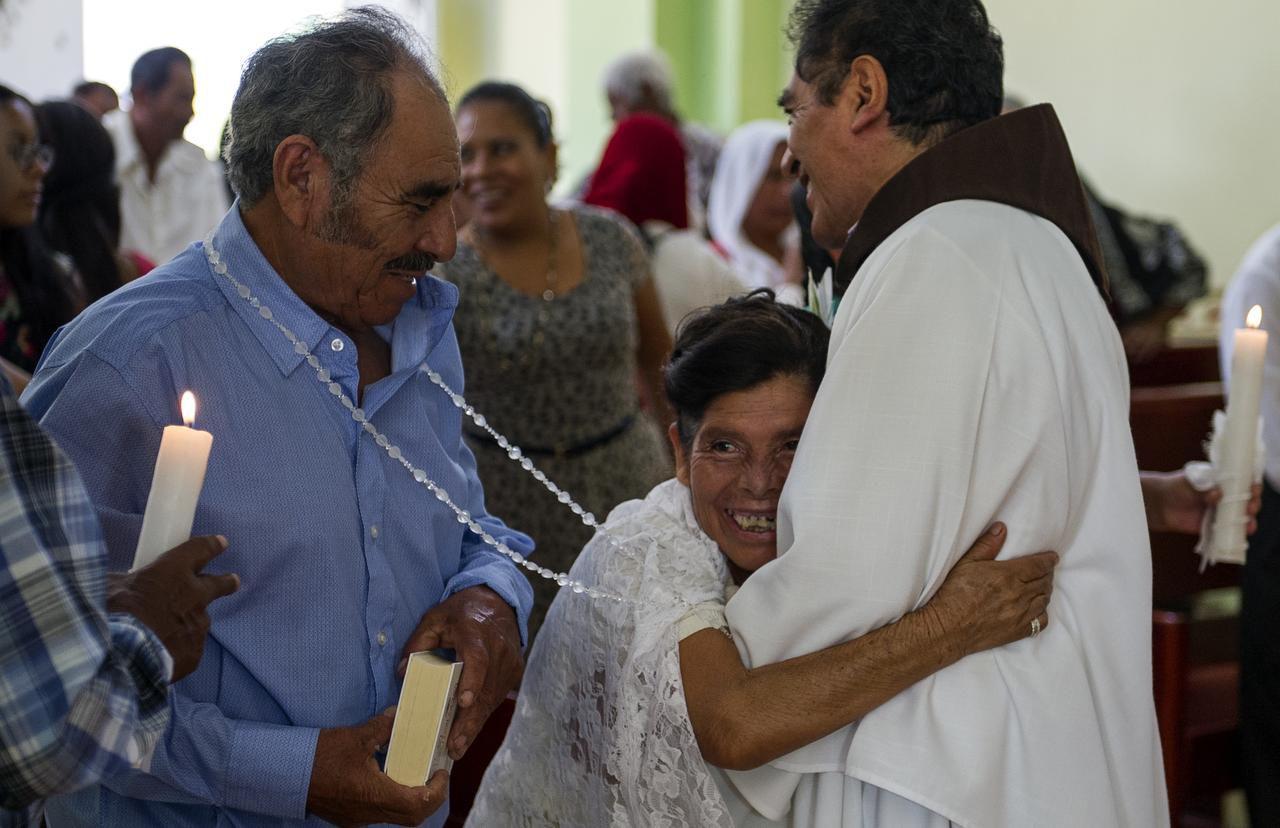 Francisca Santiago, de 65 años, abraza al sacerdote Domingo García Martínez, luego de la boda religiosa con su compañero de vida Pablo Ibarra, de 75 años, en Santa Ana, Oaxaca. (AP/NICK WAGNER)