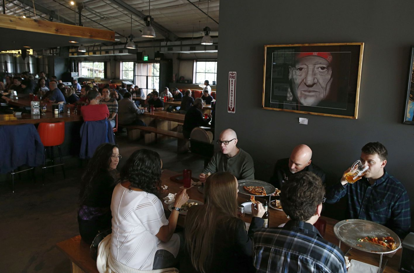 Jared Holeyfield (right) takes a sip of beer next to Darrell Caldwell (center) and Ernest Adams as they share a meal at the Austin Beer Garden Brewing Company in Austin.
