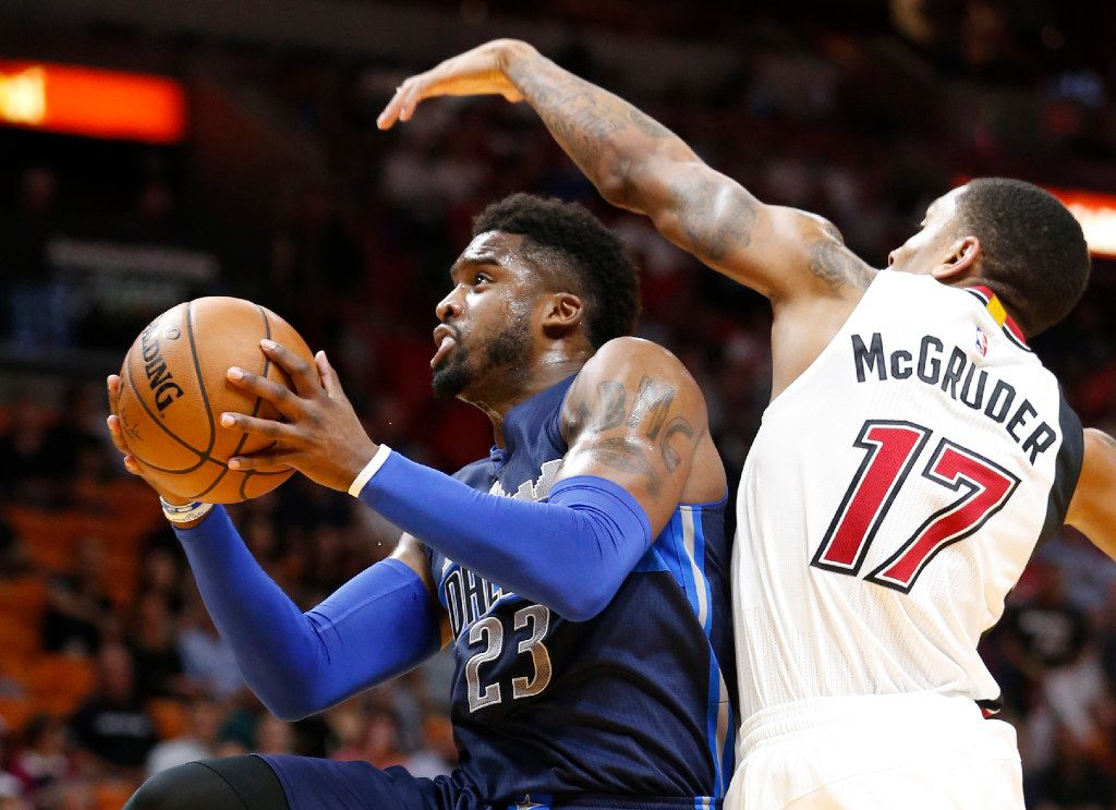 Dallas Mavericks guard Wesley Matthews (23) goes up for a shot against Miami Heat guard Rodney McGruder (17) during the first half of an NBA basketball game, Thursday, Jan. 19, 2017, in Miami. (AP Photo/Wilfredo Lee)